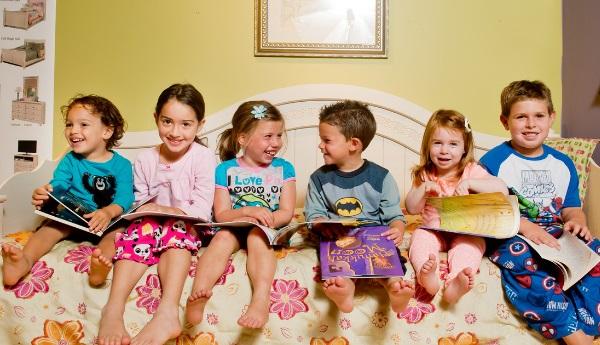 Children reading books on bed