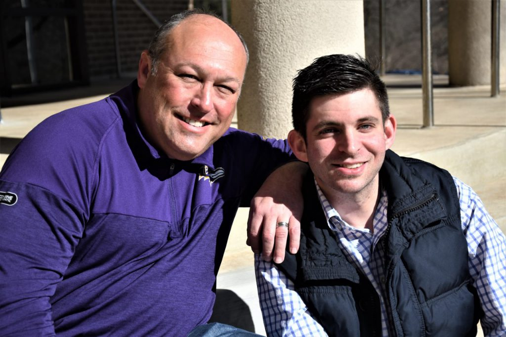 Older Man and Younger Man Smiling for Photo Outside