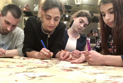 A Woman writing notes with kids on a table