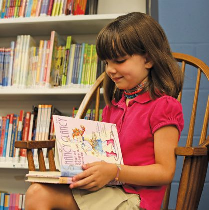 Young girl reading a book inside a library