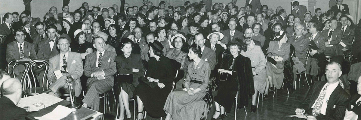 Large group of men and women seated in a room for the 1949 campaign